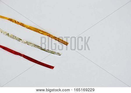golden silver and red twist tie on white background