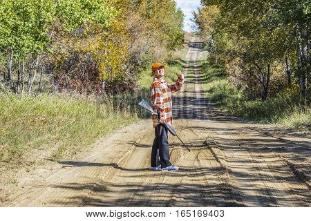 horizontal image of a woman standing on a dirt road giving a thumbs up as she is holding a shot gun ready to go hunting in summer time.