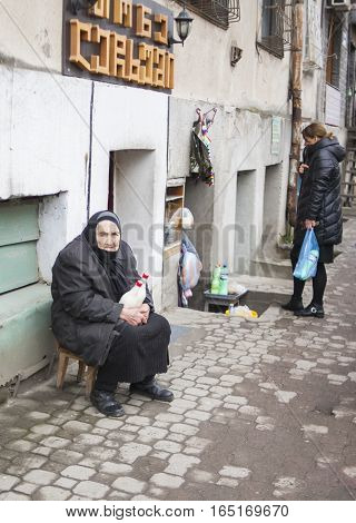 KUTAISI GEORGIA - FEBRUARY 23 2016: Old woman farmer sells his milk.