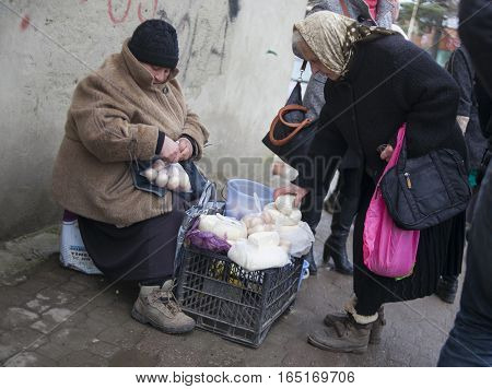 KUTAISI GEORGIA - FEBRUARY 23 2016: .Old woman farmer sells his cheese and eggs.