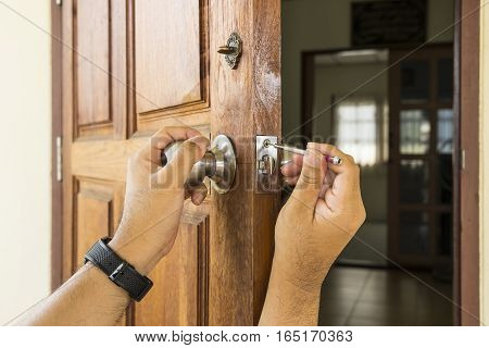 locksmith install the silver knob on old wood door by screwdriver - can use to display or montage on product