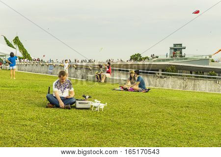 SINGAPORE - OCT 15: The man try to start Flying drone quadcopter Dji Phantom 4 Optimized Vision Positioning System on Oct 15 2016 in Marina barrage of Singapore.
