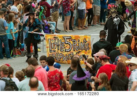 ATLANTA, GA - OCTOBER 2016: Two people in costumes carry the Little Five Points Halloween Parade banner marking the beginning of the annual event in Atlanta GA on October 15 2016.