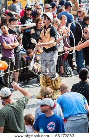 ATLANTA, GA - OCTOBER 2016:  A man on stilts juggles juggling pins while walking along the parade route of the annual Little Five Points Halloween parade in Atlanta GA on October 15 2016.