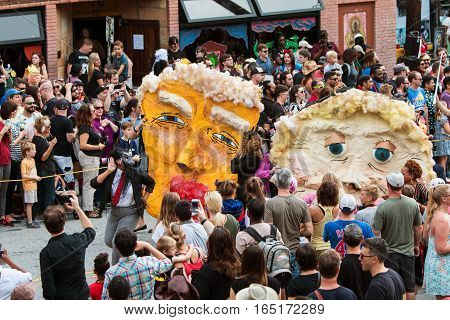 ATLANTA, GA - OCTOBER 2016:  People carry large paper mache masks that resemble Donald Trump and Hillary Clinton to parody the political candidates as part of the annual Little Five Points Halloween parade in Atlanta GA on October 15 2016.