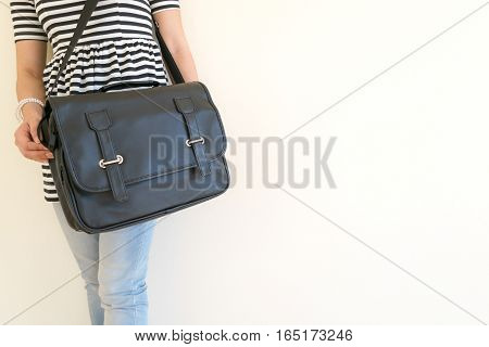 Women stand black carrying leather shoulder bag.