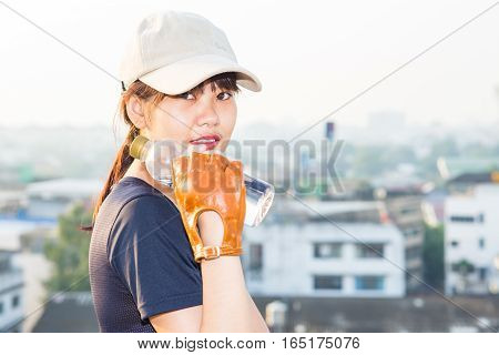 Asian sport women hold bottle of drinkking water after working out on the top of building