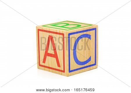 Letters A B and C imprinted on sides of single brown wooden cube on white background