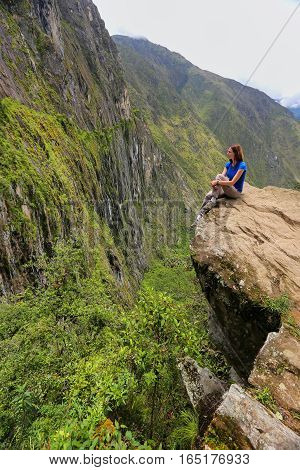Young Woman Enjoying The View Of Inca Bridge And Cliff Path Near Machu Picchu In Peru