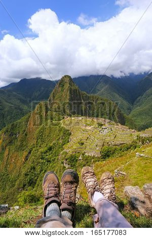 Couple of hikers resting at Machu Picchu overlook in Peru. In 2007 Machu Picchu was voted one of the New Seven Wonders of the World.