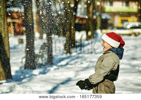 Cheerful boy in Santa hat playing with snow