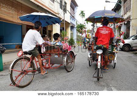 Traditional Rickshaw Driver In Penang, Malaysia