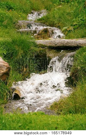 Close up view of stream flowing down the rocks surrounded by green grass