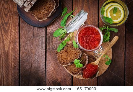 Jar With Red Caviar And Bread On Wooden Background. Flat Lay. Top View