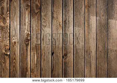 Old weathered wooden fence or wall cladding with distinctive woodgrain and knots in a full frame background texture