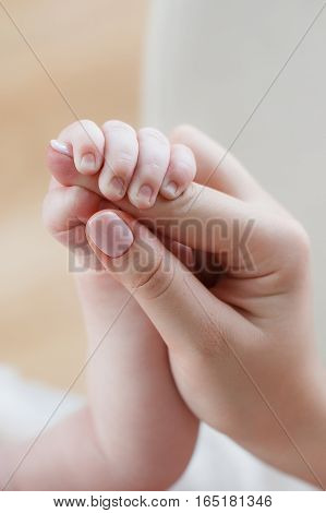 The hand of a young woman with a neat manicure and little hand of a newborn baby, the baby tightly holds mum for a finger, body parts on a light background