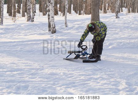 boy, checks the snowmobile, rolled down from the hill.