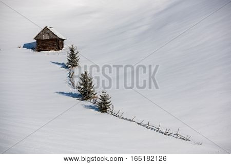 Idyllic winter landscape with small house. Hut in the mountains.