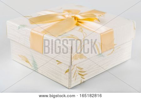 Beutiful gift box with flowers and golden ribbon