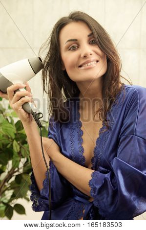 Attractive young woman blowdrying her hair. Concept of care of body.