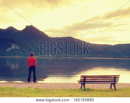 Tall Man In Red T-shirt At Wooden Bench At Mountains Lake Coast. Dark Clouds