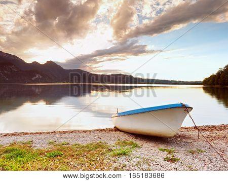 Abandoned White Paddle Boat On Alps Lake Bank. Evening Lake