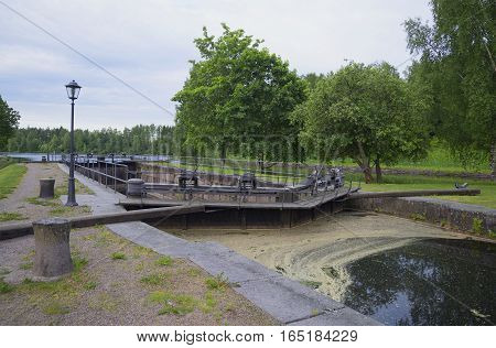 Vintage gateway on the Saimaa canal, cloud on a summer morning. Finland