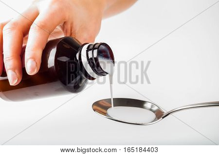 pour liquid medicine in metal spoon by hand