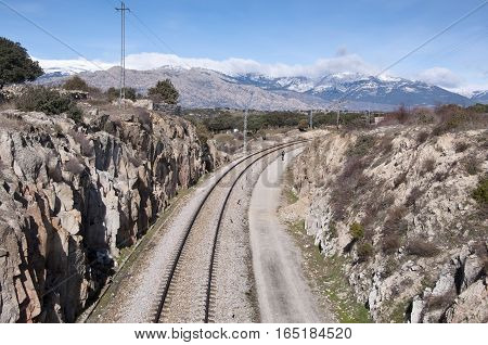 Cycling next to the railroad. At the background snow capped peaks of the Guadarrama Mountains. Photo taken in Colmenar Viejo Madrid Province Spain