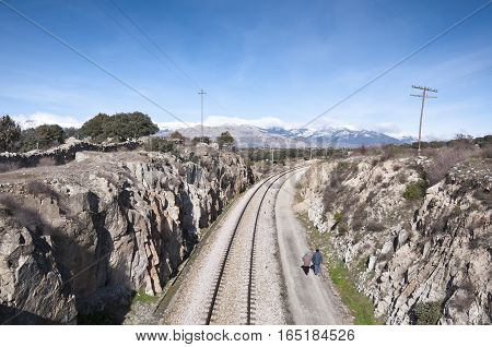 Walking next to the railroad. At the background snow capped peaks of the Guadarrama Mountains. Photo taken in Colmenar Viejo Madrid Province Spain