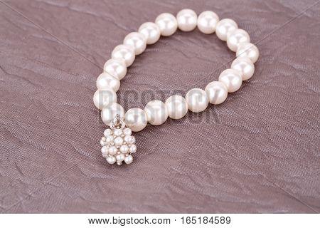Stylish bracelet with pearls on fabric background.
