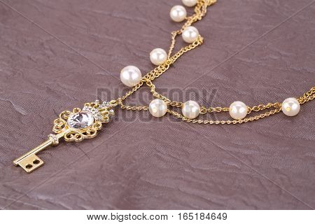 Stylish necklace with pearls and key on fabric background.