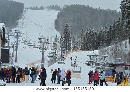 BUKOVEL, UKRAINE - December 2, 2016: Snowboarders and skiers standing in a line in front of ski lift. Bukovel is the most popular ski resort in Ukraine. Winter ski season and Winter sports concept