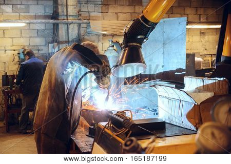 Working welder welds the parts. A process using a semi-automatic welding.