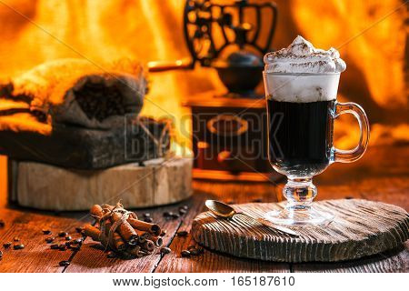 Irish coffee cocktail on rustic wooden board. Coffee grinder and sack of beans. Fireplace on the background