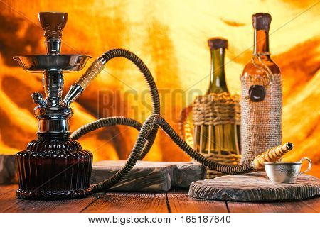 Nargile and wine in the light of fireplace on the wooden table. Oriental cafe concept