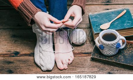 Feet and hands of person wearing one winter sock, knitting the other one and drinking tea