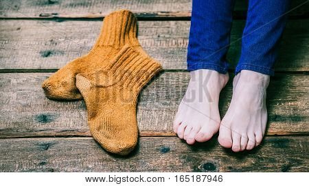 Bare female feet and brown wool socks laying on the wooden floor. Closeup view