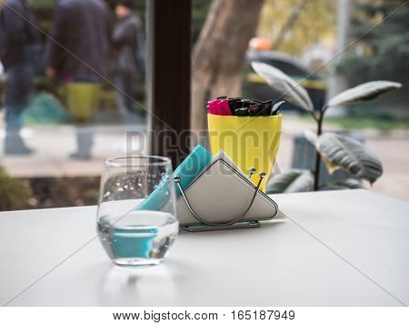 Picture of the napkin holder near a glass of water and yellow cup against the blurred background of landscape outside the cafe room. Selective focus on napkin holder with white and turquoise napkin.