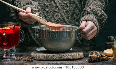 Mulled wine in the pan and spices on the table. Human hands pouring prepared mulled wine into irish glasses. Rustic style. Front view