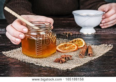 Human hands holding cup of tea behind honey jar and spices on the table. Front closeup view