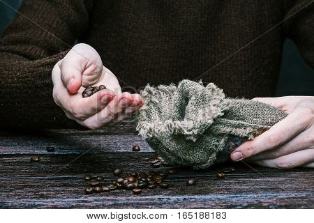 Human hands pouring coffee beans into jute sack. Front view