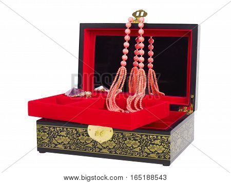 Picture of the opened jewel-box with red fit-out. Wooden jewel-box with pink coral bead necklace isolated on white background. Side view.