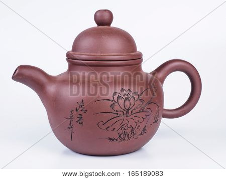 Picture of the brown infuser teapot. Infuser teapot on white background. Handmade earthenware. Side view.