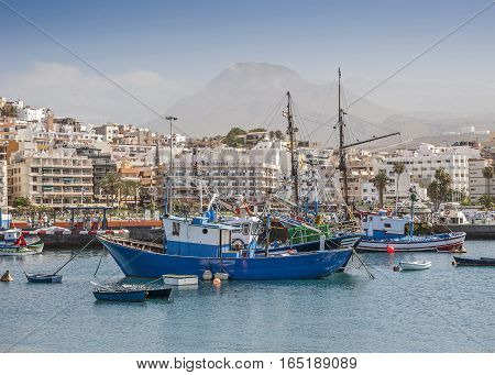 Island Spain Tenerife rowing boats of all sizes and large fishing boats in the port city the promenade in Los Cristianos.