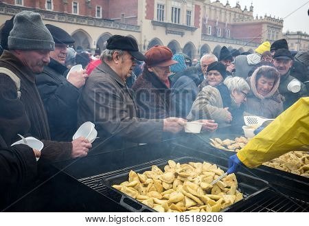 CRACOW POLAND - DECEMBER 18 2016: Christmas Eve for poor and homeless on the Central Market in Cracow. Every year the group Kosciuszko prepares the greatest eve in the open air in Poland