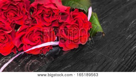 Red roses on wooden background. Holliday background.