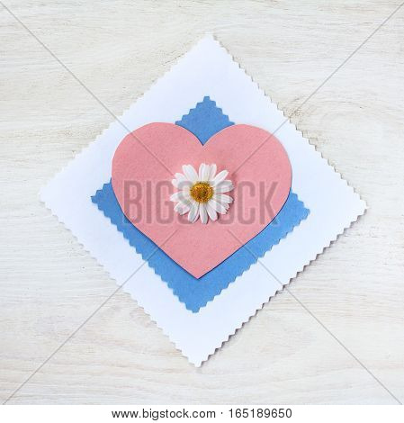 flat layout of daisy flower on heart symbol top view / Valentine card for the holiday