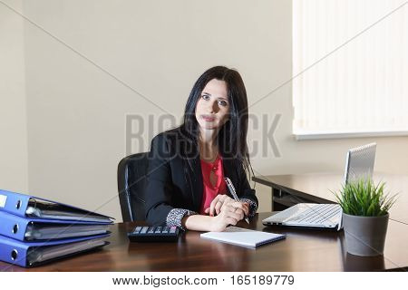 Young attractive woman in a business suit taking notes in Notepad at Desk in office