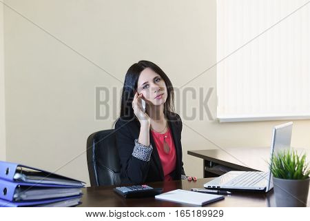 Young attractive woman in a business suit talking on phone at Desk in office